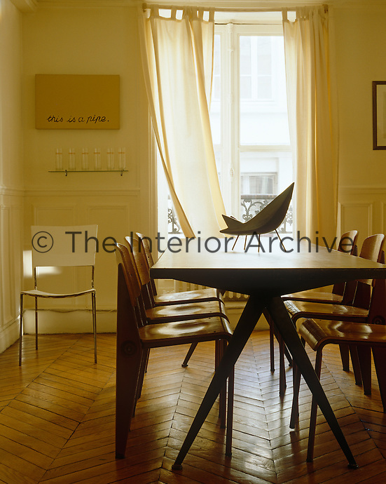 A Compass table surrounded by Standard chairs, by Jean Prouve furnish this light and airy dining room