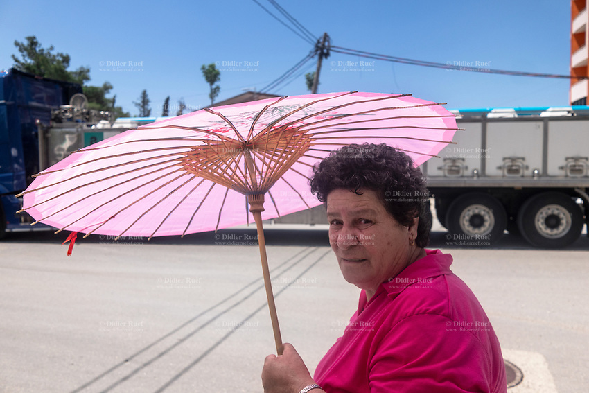 Albania. Vlorë. An elderly woman walk on the sidewalk and protects herself from the sun under a pink Chinese umbrella. Truck on the road. Vlorë is the third most populous city of the Republic of Albania. 25.2018 © 2018 Didier Ruef