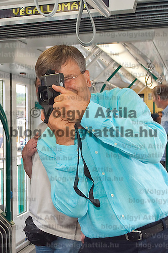 Budapest city mayor Gabor Demszky takes photos with his analogue Hasselblad camera on board the newly started Combino tram in Moszkva square, Budapest, Hungary. Saturday, 01. July 2006. ATTILA VOLGYI