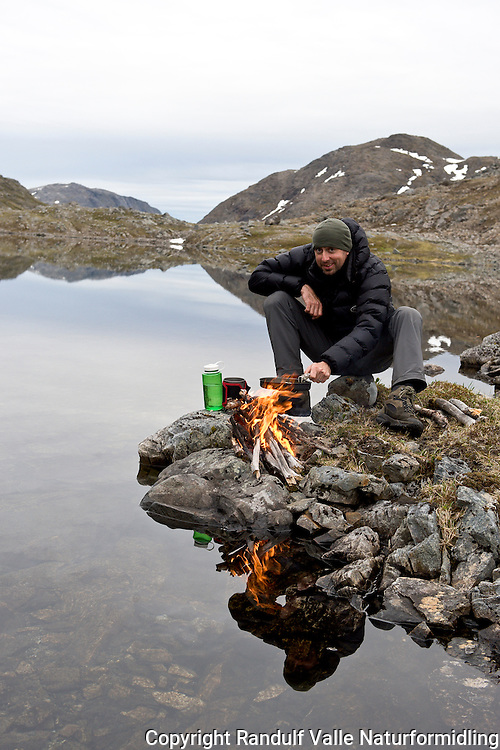 Mann fyrer bål i vannkanten. ---- Man and camp fire.
