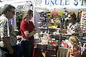 Vendor showing items for sale at his booth, at Silverdale, WA Whaling Days event. Stock photography by Olympic Photo Group