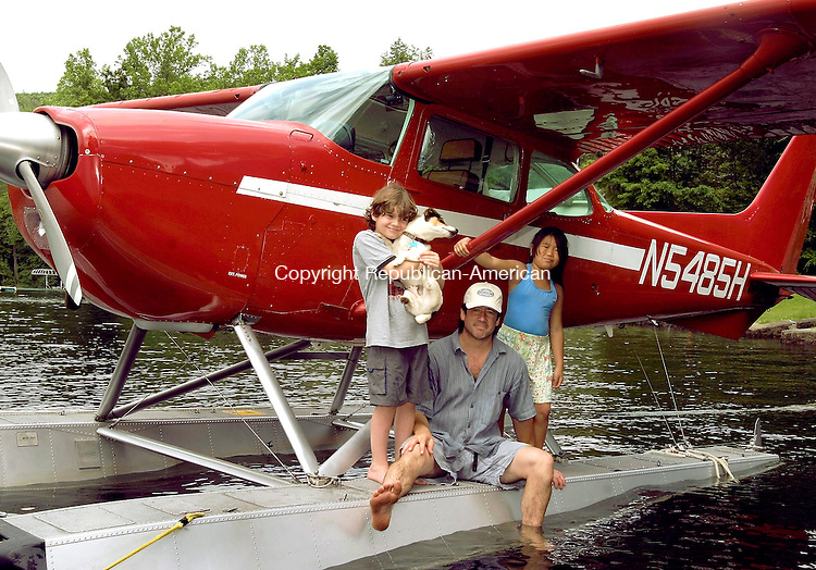 WINSTED, CT - 10 JUNE 2005 -061005JS06--Winsted resident Jim Seaver, center,  sits on the floats of his sea plane with his son James, 9 and daughter Olivia, 7, at Highland Lake in Winsted on Friday. Highland Lake is offically classified as an airport through the efforts of Seaver. --Jim Shannon Photo-- Jim Seaver, James Seaver, Olivia Seaver, Highland Lake, Winsted are CQ