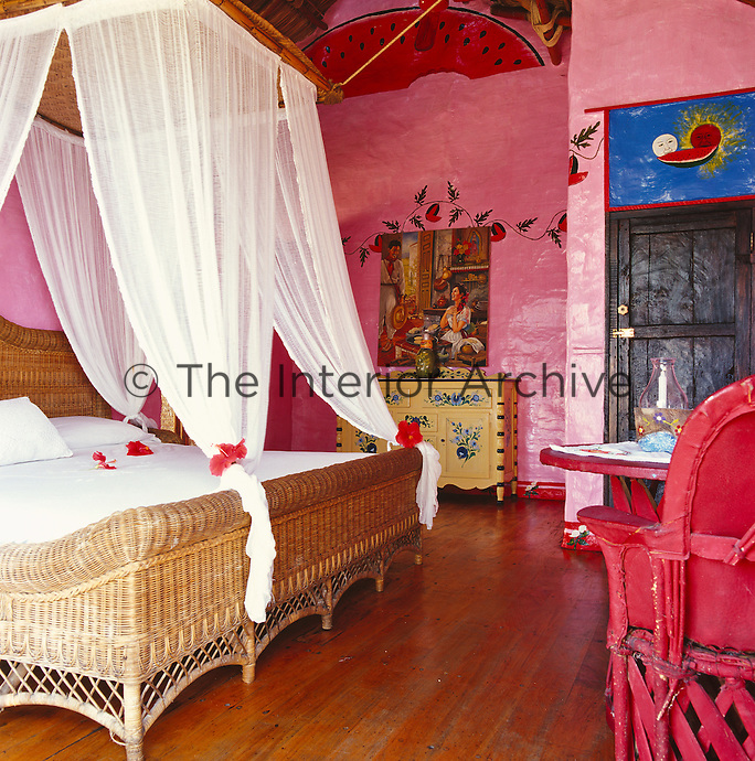 This bedroom has pink walls decorated with hand-painted motifs and a large wicker bed with a canopy