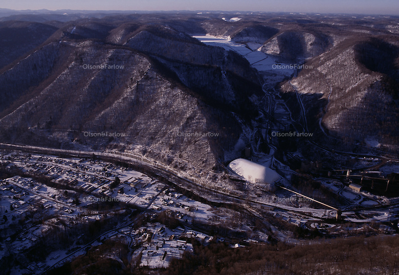The town of Sylvester sits under an impoundment that could break spilling toxic sludge into the valley below. The community sued the coal company to keep from being buried in coal dust and a white plastic bubbler covers a processing plant.