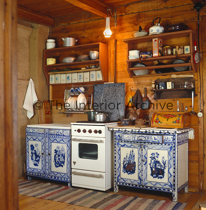 A rustic kitchen with an old stove flanked by a pair of cupboards which have been painted with motifs of blue and white tiles