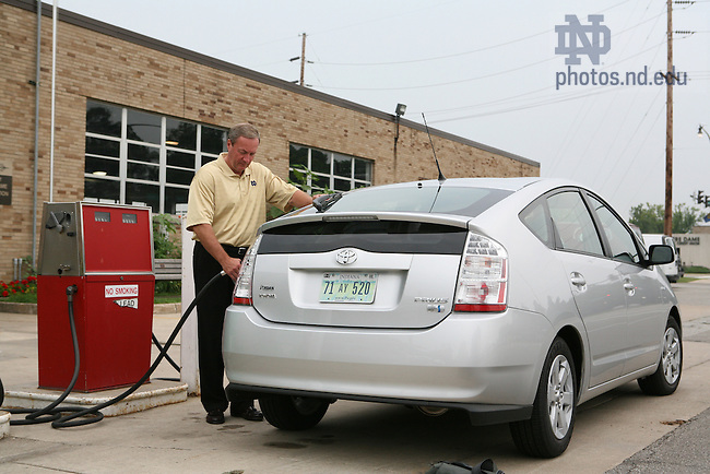 Notre Dame Vice President for Business Operations James Lyphout tops off the gas tank in the University's Toyota Prius Hybrid car.