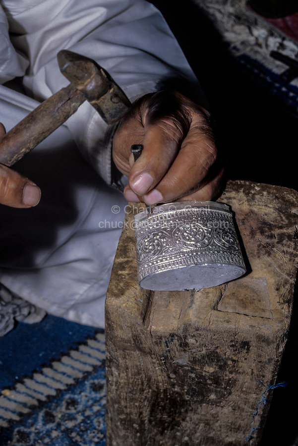 Rustaq, Oman.  Rashid al-Obeidani, Silversmith, in his Workshop, Hammering a Design on to a Khanjar (Dagger).