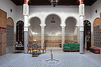 Ground floor central courtyard with a fountain in the centre, zellige tile decoration and a recessed seating area with 3 fluted horseshoe arches, in a typical Tetouan riad, a traditional muslim house built around a courtyard, built in Moorish style with strong Andalusian influences, next to the Great Mosque or Jamaa el Kebir in the Medina or old town of Tetouan, on the slopes of Jbel Dersa in the Rif mountains of Northern Morocco. Tetouan was of particular importance in the Islamic period from the 8th century, when it served as the main point of contact between Morocco and Andalusia. After the Reconquest, the town was rebuilt by Andalusian refugees who had been expelled by the Spanish. The medina of Tetouan dates to the 16th century and was declared a UNESCO World Heritage Site in 1997. Picture by Manuel Cohen