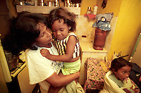 Somália da Silva comforts daughter Jessica in the kitchen of the family home while Aline, right, waits for lunch. Pregnant with a first child at 15 — a son taken by his father shortly after birth — Somália had no idea modern birth control existed until pregnant with her seventh child. She tried birth control pills, but poor education led to improper use and an eighth child. The da Silvas planned for Somália to have her tubes tied following her latest pregnancy.