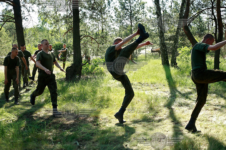 Young soldiers stretching up at the practice range. This year's class of drafted recruits is the final one after 90 years of compulsory military service, as Poland's army turns professional in 2009.