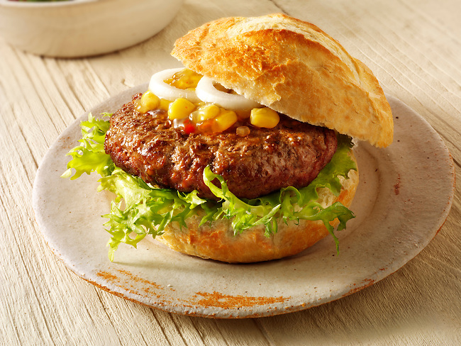 Home made burger in a crusty roll with sweetcorn relish and omion photo. Funky Stock Photos
