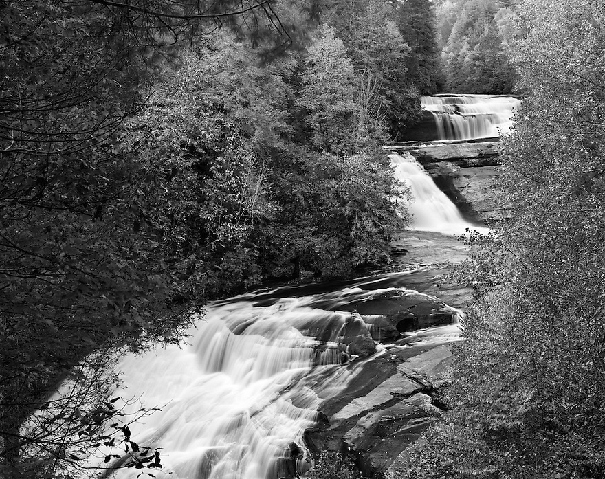 """""""Triple Falls""""<br /> DuPont State Forest <br /> Brevard, North Carolina<br />  2014<br /> After a short moderate hike, Triple Falls come into view.  It is easy to understand how Triple Falls got its name.  It has a three-level drop totaling about 100 feet.  The two upper falls drop about 25 feet each, while the lower falls descend about 45 feet.  There are numerous flat rocks to walk on, making this area very popular with sun worshippers and waterfall enthusiasts. These falls were featured in the movie The Last of the Mohicans.<br /> <br /> 4 x 5 Large Format Film"""