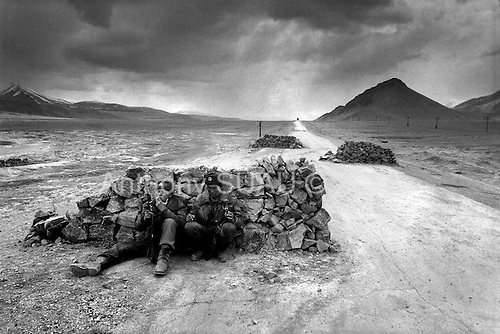 """Horag-Osh Road, Tajikistan .1996.Russian border guards monitor the old silk road which has become a main route for Afghan grown opium since the fall of the former Soviet Union. Soldiers search tranport trucks for hidden """"hannka"""" or raw opuim.."""