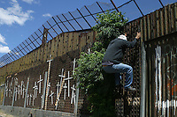 An ilegal inmigrant tries to jump over the wall or fence separating the city of  Nogales, Sonora, in North Mexico, with the USA.