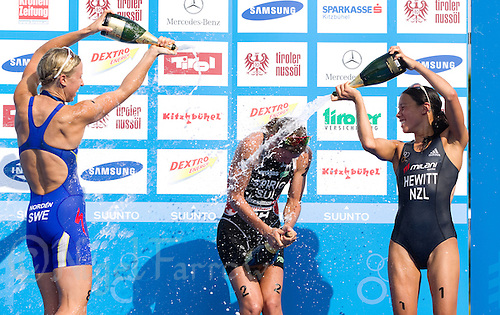 23 JUN 2012 - KITZBUEHEL, AUT - Nicola Spirig (SUI) of Switzerland (centre) struggles to open her bottle of champagne after winning the elite women's 2012 World Triathlon Series round in Schwarzsee, Kitzbuehel, Austria, as she celebrates with silver medalist Lisa Norden (SWE) of Sweden (left) and bronze medalist Andrea Hewitt (NZL) of New Zealand (right) (PHOTO (C) 2012 NIGEL FARROW)