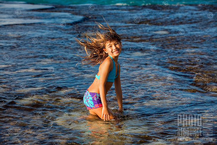 A young girl plays in the surf on a windy day at a North Shore beach on O'ahu.