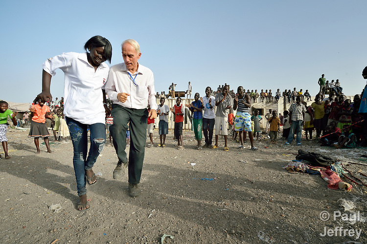 Father Mike Bassano, a Maryknoll priest from the United States, dances with members of a Catholic dance group inside a United Nations base in Malakal, South Sudan. More than 20,000 civilians have lived inside the base since shortly after the country's civil war broke out in December, 2013, but renewed fighting in 2015 drove another 5,000 people into the relative safety of the camp. Bassano, also a member of Solidarity with South Sudan, lives in the camp to accompany the people there.