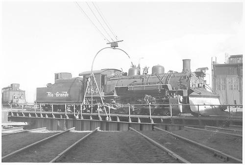 Engineer side view of K-36 #484 with plow on turntable at Alamosa.  Roundhouse is in background.<br /> D&amp;RGW  Alamosa, CO  Taken by Richardson, Robert W. - 1955