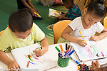 Education Preschool 3-4 year olds classroom scene boy and girl sitting side by side art activity drawing with markers boy using left hand girl using right hand