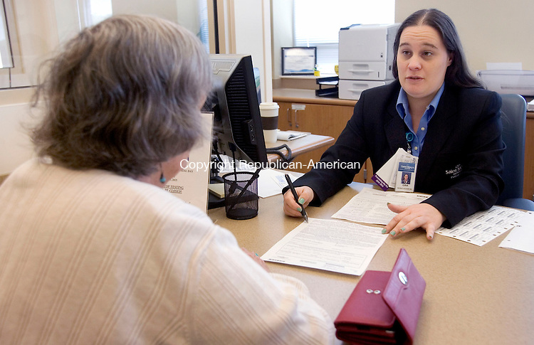 WATERBURY CT. 08 May 2015-050815SV08-From left, Joan Vaughan of Southbury registers with Gina Urbano, a patient access representative, at St. Mary&rsquo;s Hospital in Waterbury Friday. <br /> Steven Valenti Republican-American