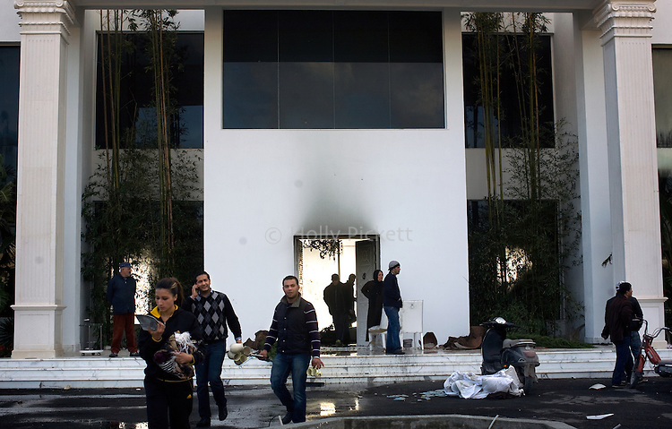 Looters leave the the home of a relative of Tunisian President Zine el-Abidine Ben Ali with dishes and other souvenirs in Hammamet, Tunisia, about an hour's drive from the capital of Tunis, Thursday, Jan. 13, 2011. Ben Ali resigned and fled to Saudi Arabia the following day.