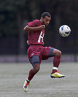 Harvard University midfielder Andrew Wheeler-Omiunu (18) clears the ball. Boston College (white) defeated Harvard University (crimson), 3-2, at Newton Campus Field, on October 22, 2013.