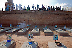 A crowd begins to gather before the burial of eight bodies found last week in a mass grave near the town of Al-Qala in the Nefusa Moutains, Libya, in the new cemetery overlooking the town on Friday, Sept. 30, 2011. The eight were reburied next to 35 bodies found in a separate mass grave in the area. Members of the Amazigh indigenous tribe, the men were arrested from their homes and at checkpoints by pro-Gaddafi forces, imprisoned, and finally executed sometime in June. The men, many of them related as fathers and sons, or as brothers, were missing until the first, larger mass grave was found in mid-August.