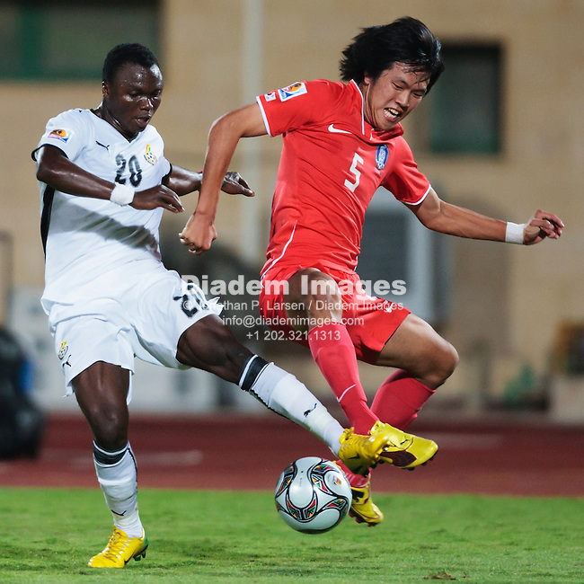 SUEZ, EGYPT - OCTOBER 9:  Young Won Kim of South Korea (R) defends against Dominic Adiyiah of Ghana (L) during the 2009 FIFA U-20 World Cup quarterfinal match at Mubarak Stadium on October 9, 2009 in Suez, Egypt.  Editorial use only.  No pushing to mobile device usage.  Commercial use prohibited.  (Photograph by Jonathan Paul Larsen)