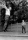 United States President Gerald R. Ford, left, tries to leap off the trampoline at Camp David near Thurmont, Maryland on September 2, 1974.  His daughter, Susan Ford, right,  is watching from the ground.<br /> Mandatory Credit: David Hume Kennerly / White House via CNP