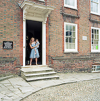 Francesca Rowan with her son in her arms stands at the entrance to Lamb House, once the home of Henry James