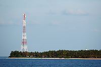 Radio tower sticks out from an island densely covered with palm trees, Maldives.