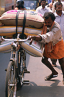 A man pushing a bicycle laden with heavy sacks up a hill in Trivandrum, South India.
