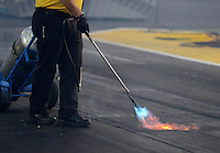 Sept. 28, 2012; Madison, IL, USA: NHRA Safety Safari member puts some heat in the starting line area with a torch during qualifying for the Midwest Nationals at Gateway Motorsports Park. Mandatory Credit: Mark J. Rebilas-