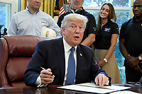 United States President Donald J. Trump signs the National Manufacturing Day Proclamation in the Oval Office of the White House in Washington, DC on Friday, October 6, 2017.<br /> CAP/MPI/CNP/RS<br /> &copy;RS/CNP/MPI/Capital Pictures
