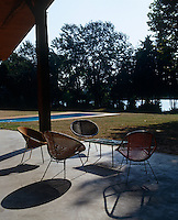A group of contemporary wicker chairs on the terrace overlook the swimming pool and the River Lot