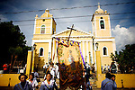 During the Santa Ana Day festival at the Santa Ana Catholic church in Chinandega, Nicaragua, a flag with a picture of Ana is carried out of the church into the evening sun ahead of a statue of the saint.  According to the tradition, Santa Ana is the mother of the Virgin Mary and grandmother of Jesus Christ.