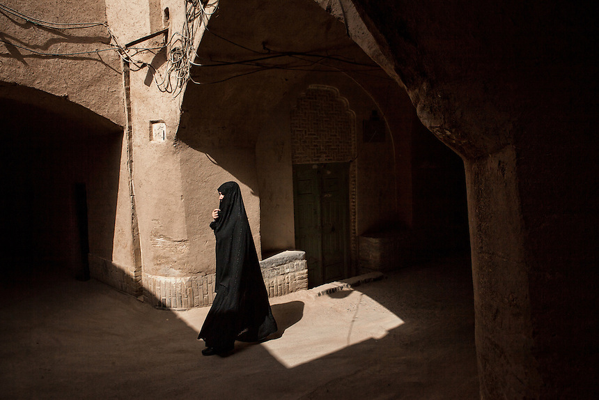 an Iranian woman pass through the alleyway of the old city of Yazd. Yazd is one of the oldest living city in the world. Yazd was visited by Marco Polo in 1272, who described it as a good and noble city and remarked its silk production. The name Yazd means worship. And badgir is one of distinctive feature of this city.