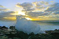 waves splash the rocks as a beautiful sunset and clouds paint the sky
