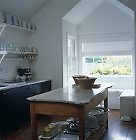 A collection of bowls, dishes, glassware and containers is stored on the shelves and beneath an old French farmhouse table in this kitchen
