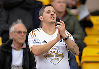 A Swansea City fan applauds his team during the Barclays Premier League match between Norwich City and Swansea City played at Carrow Road, Norwich on November 7th 2015