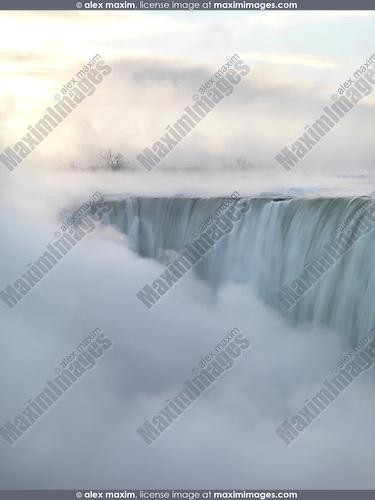 Niagara Falls covered in thick white mist, Canadian Horseshoe, beautiful sunrise scenery in soft light pastel colors, wintertime scenic. Niagara Falls, Ontario, Canada.