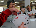 Seniors citizens pass the time playing cards,  Tuesday, Nov. 1, 2011, at a shelter at LP Wilson Community Center in Windsor Conn.  Connecticut Governor Dannel P. Malloy toured telling the 300 people using the center everything possible is being done to restore power. The unseasonably early nor'easter Saturday had utility companies struggling to restore electricity to more than 3 million homes and businesses. in the northeast.  Seen here are, Charlotte Sacchitella, left, Gabrielle Geoffroy, center, and Jo Baral, right, not shown holding the cards in the foregound is Joan Rhodes, all of Windsor. (Jim Michaud/Journal Inquirer) . .