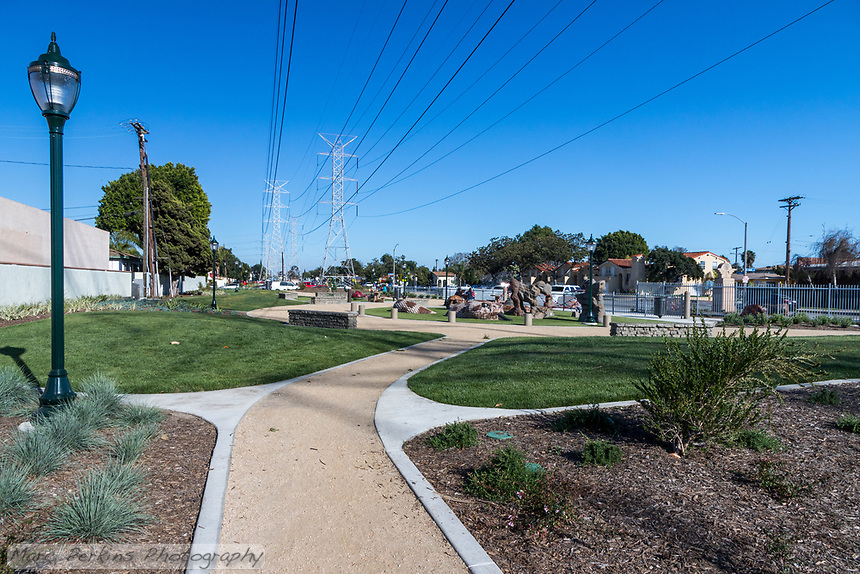 A view of the western portion of State Street Park, featuring the decomposed granite trail, lawns, drought-resistant landscaping, and the reptile play structures all underneath the soaring power lines.