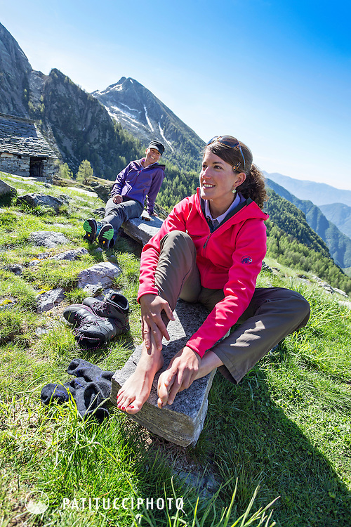 A woman hiker sits outside a hut taking her shoes off and rubbing her sore feet