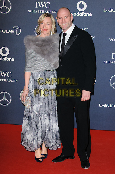 Alice & Lawrence Dallaglio .Arrivals at the Laureus 2012 World Sports Awards held at the Queen Elizabeth II Centre, London, England..February 6th, 2012.February 6th, 2012.full length black suit grey gray dress wrap married husband wife .CAP/CJ.©Chris Joseph/Capital Pictures.