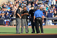 Home plate umpire Mike Estabrook, third base umpire Jeff Gosney and Bulls trainer check on first base umpire A.J. Johnson after he was hit in the head on an attempted pickoff during a game between the Empire State Yankees and the Durham Bulls  at Durham Bulls Athletic Park on June 8, 2012 in Durham, North Carolina . The Yankees defeated the Bulls 3-1. (Tony Farlow/Four Seam Images).