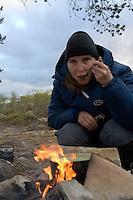 Jente lager pasta i gryte på bål ---- Girl making pasta in pot on camp fire