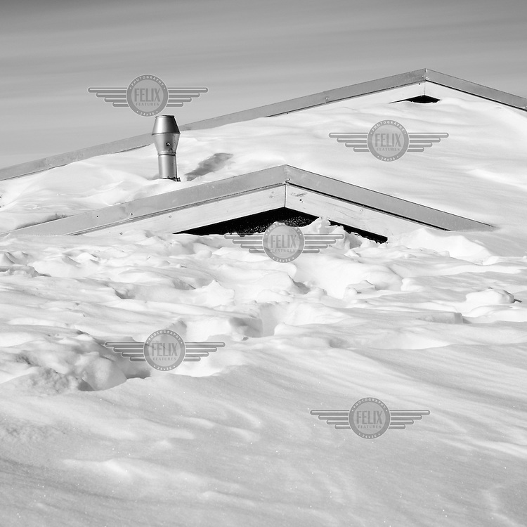A house completey submerged in snow, with only the roof and the chimney poking out of the snow. Established on the east coast of Greenland in 1950, Daneborg is the base for the Sirius Patrol, a Danish navy unit which patrols and enforces Danish sovereignty in the Arctic regions of Northern and Eastern Greenland.