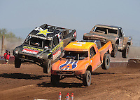 Apr 17, 2011; Surprise, AZ USA; LOORRS driver Adrian Cenni (11) races alongside Todd Leduc (4) as Steve Barlow (83) follows during round 4 at Speedworld Off Road Park. Mandatory Credit: Mark J. Rebilas-