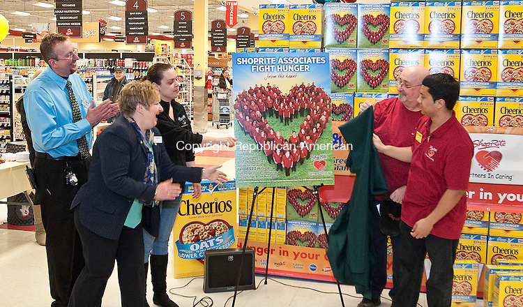 WATERBURY, CT-032814JS01-ShopRite associates Lyndsay McKenzie-cashier, third from left; Joseph DeLucia-Deli and Foods-to-Go, second from right, and Manuel Vega-Service Clerk, right, unveil the back of a Cheerios box that features their photo, with other ShopRite associates, as store manager Jon Murphy, left, ad Community Liasion Mary Low Grendeiszwski, second from left, look on during a ceremony at the Wolcott Street location on Friday. The three associates from the Waterbury location was one of 40 winning ShopRite stores across six states in the ShopRite Partners in Caring Competition.  <br /> Jim Shannon Republican-American